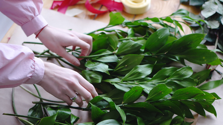 The hands of the florist are holding greens on an empty sheet of craft paper for the arrangement of a bouquet