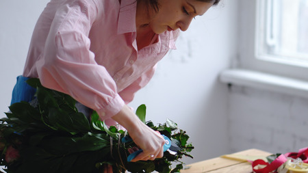 Professional floral artist, florist cutting flower stems at flower shop. Floristry, handmade and small business concept