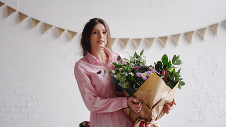 Portrait of florist with big modern bouquet of different flowers