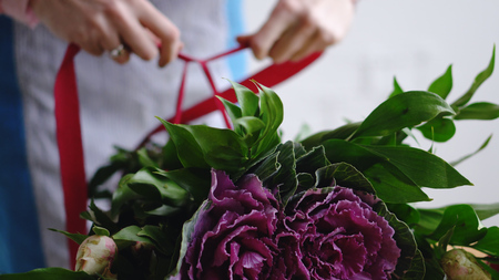 Professional florist artist swathes with a ribbon bouquet in the background Banco de Imagens
