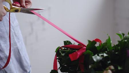 Florist cuts the red ribbon on the bouquet with scissors