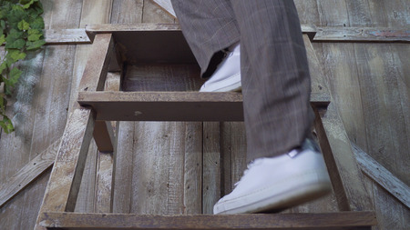 A girl in trousers and sneakers rises to a wooden stepladder: legs close-up photo