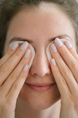 Cute young woman with clean face skin removes makeup from eyes with cotton pads. Makeup remover. Cosmetic skin care