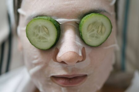 Relax and skin care. Moisturizing and lifting bags under the eyes with the help of green cucumbers. Natural cosmetic procedure Фото со стока