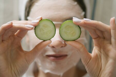 Beautiful skin care - a young woman in a white moisturizing mask puts round cucumbers on her eyes, lying on a couch