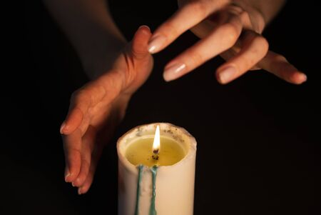 Mysterious magic close-up - womens hands conjure over a burning candle in isolation on a black background. The concept of prediction, clairvoyance and divination Stockfoto