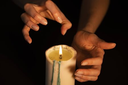 Hands conjure over a candle on a black background, close-up. Spiritual session, clairvoyant fortune teller at work.