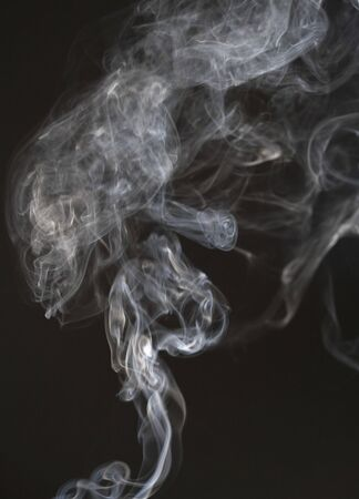 White smoke dissolves on a black isolated background. Steam or fog in the air