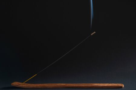 Incense burns on a beautiful wooden stand, on a black background. Aromatherapy for health and prosperity. The concept of meditation, zen and self-knowledge Foto de archivo