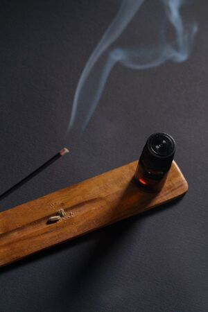 Aromatic oil and steaming incense on a wooden stand. Concept of aromatherapy and massage