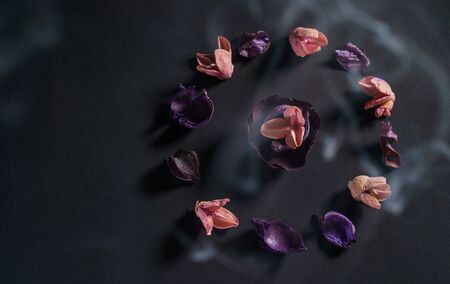 The culture of zen and meditation. A circle of dry flowers on a dark background. A copyspace for your text. The concept of aromatherapy and spa. Thin smoke flies over the flowers