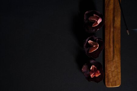 Eastern aromatherapy. Dry flowers and steaming incense on a dark background. Copyspace for your text Stock Photo