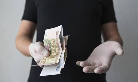 A doctor in medical gloves holds Russian rubles. Very little money, the concept of bribery and corruption