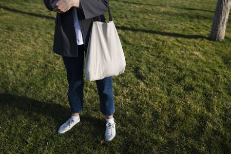 A woman in jeans holds a beige cotton bag in her hands and standing in the park on the lawn. Natural eco-friendly bag made from recycled materials. Stock Photo - 143223309