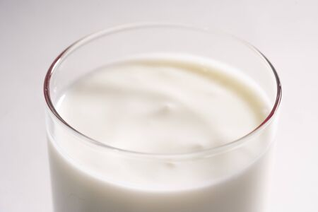 Glass of fresh vegetarian yogurt on coconut milk. Eco milk in a transparent glass on a white background, isolated.