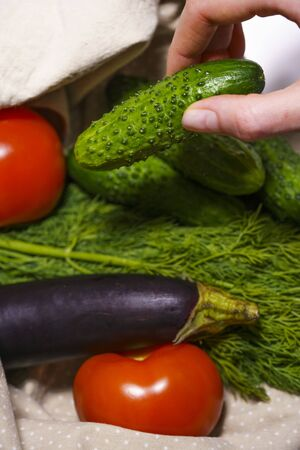 Lifestyle without plastic, the concept of caring about the environment. Fresh vegetables are taken from a cotton eco bag of beige color close-up