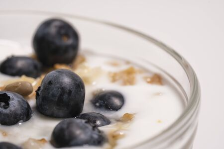 Blueberries in vegan yogurt in a transparent glass, healthy breakfast. Add the berry-shaped vitamins to the milk dessert. Close-up 免版税图像