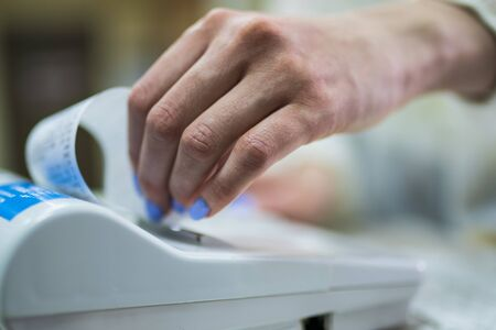 The seller rips off and checks the check close-up. White cash register close-up