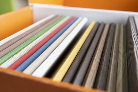 Colored furniture panels in a box. Examples of wooden decor finishes of different colors