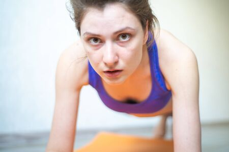 A woman stands on her elbows, raises her head and looks at the camera. Focus, balance, and endurance when doing a plank close-up at home