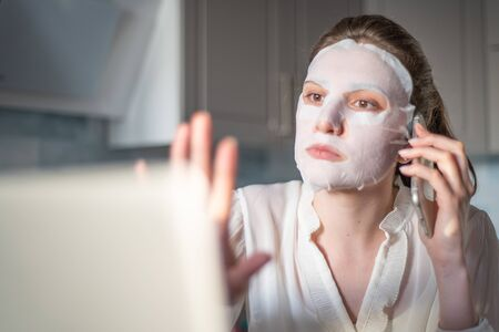 Lazy freelancer girl. Freelancer at home solves work problems on the phone with a moisturizing mask on her face 版權商用圖片