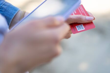 Id qr. Person scans the qr code on a plastic card with his phones camera. Modern fast technology