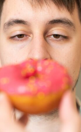 Man with donut. Pink bad fat doughnut in the hands of a man. A quick snack, excess cholesterol