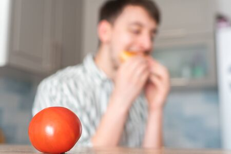 The man chose an unhealthy lifestyle. Guy eats burger on the background fresh tomato