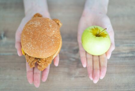 Choose between a calorie burger and a green apple. Womens hands hold harmful and healthy food