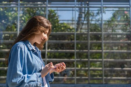 5g phone. Millennium young woman communicates by phone while walking in a green city. Girl walks by, looking at the phone