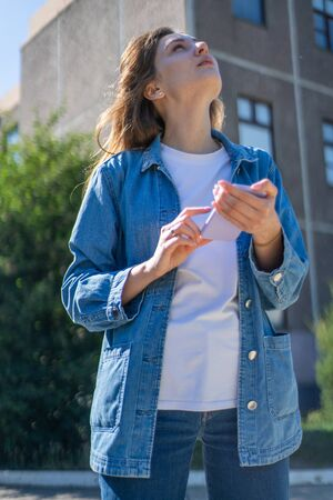 5g. Beautiful woman in sunshine sends files through smartphone at high speed and looks up