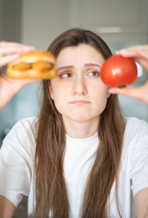 Temptation of junk food. The girl is thinking about what to eat. A beautiful woman holds a tomato and cheeseburger and looks at them Standard-Bild