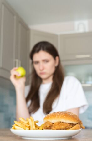 Vegan woman eats an apple against the backdrop of unhealthy fast food. Choosing the right food Standard-Bild