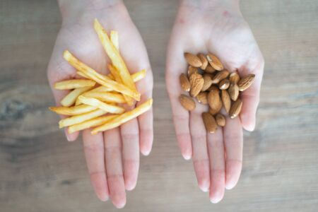 Choosing healthy or harmful food. Almond nuts or French fries in hands