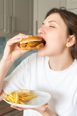 Uncontrolled overeating. A woman eats a cheeseburger. Burger with meat in the hands of a girl
