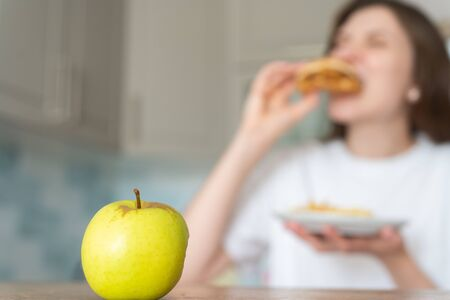 Unhealthy food choices. Wrong nutrition and overeating. Woman eats cheeseburger and fries against apple Standard-Bild