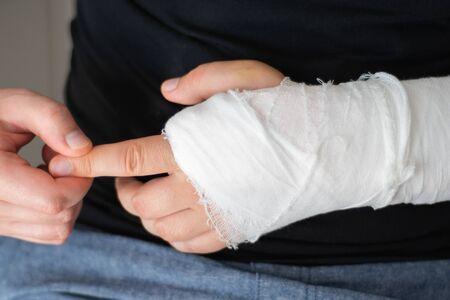Rehabilitation after a broken arm. A man massages his hand in gypsum, close-up