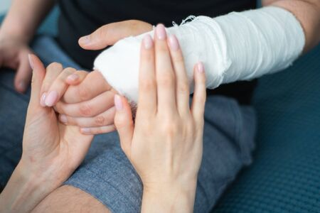 Checking hand in bandage. Patient with fracture at doctors visit Standard-Bild