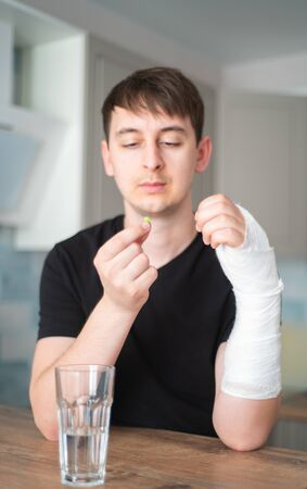 A man with a broken hand drinks painkillers. Temporary health problems. Hand in gypsum Standard-Bild