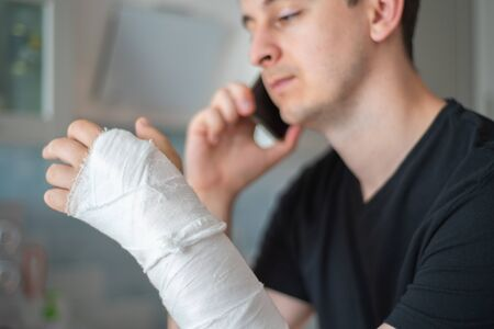 The person with a broken hand speaks on the phone. Working as a freelancer during a sick leave Standard-Bild
