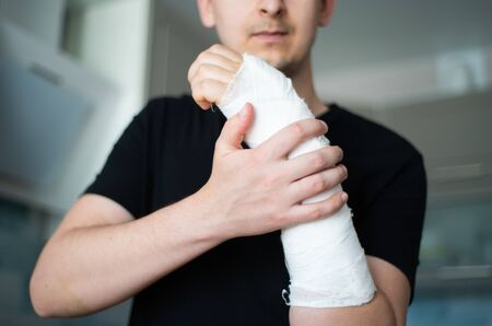 A young man checks the plaster bandage for strength by touching a broken arm close-up Standard-Bild