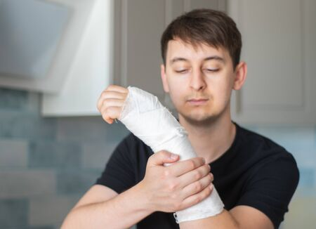 The guy makes a visual check of his plaster bandage, touching a broken arm and looking at the plaster. Painful sensations from touching a fracture arm