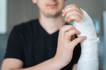 Itching under bandage. Man tries to scratch broken arm, close-up Standard-Bild