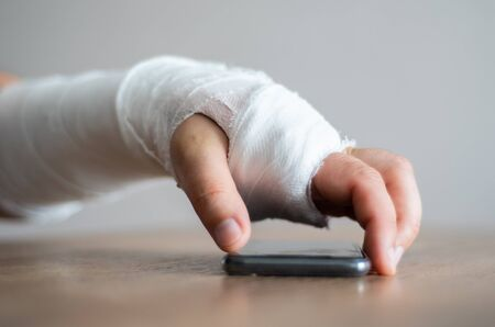 Person with a fracture is trying to take the phone to answer the call. Discomfort from injury, pain in sick arm