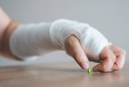 Broken hand in bandage tries to take a painkiller. Stress and pain after injury