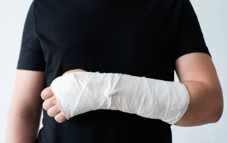 A broken hand in a gypsum bandage. Painful heavy movements of broken finger hands close-up Standard-Bild