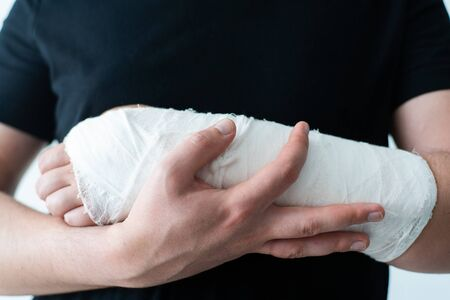 A healthy hand of a young man supports a wounded broken arm in a plaster bandage close-up. The difficulty of self-movement of the hand at a fracture