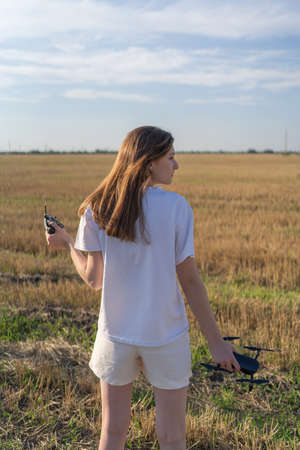The female drone pilot walks into the field and inspects before the flight. Drone in womens hands