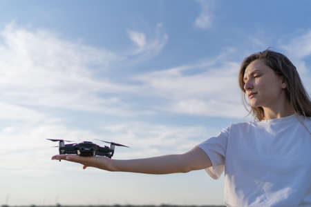The girl is a drone pilot holding a working drone on her hand at sunset. Working propellers of a small quadcopter in womens hands Standard-Bild