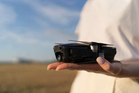 A small drone in hands. Electronic gadget for work and hobby. Quadcopter operator with device